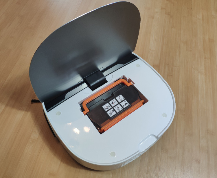 The robot vacuum under the lid with the dustbin installed